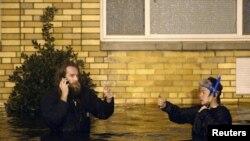 兩名男子星期一在紐約布魯克林被洪水淹沒的街道上涉水