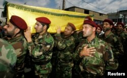 FILE - Hezbollah members attend the funeral of a Hezbollah fighter who died in the Syrian conflict, in Beirut, May 26, 2013. Authorities in Kabul and human rights groups have roundly criticized Iran for sending Afghans living in Iran to Syria to fight alongside Hezbollah and Iranian forces in support of the Assad government.