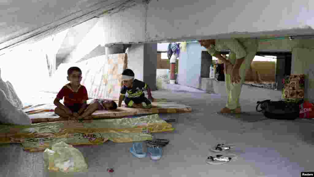 Iraqi Christian children, who fled the violence in the village of Qaraqosh, sit on a mattress at their makeshift shelter in an abandoned building in Irbil, north of Baghdad, Aug. 11, 2014.