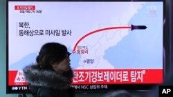 Una mujer en una estación de tren en Seúl, Corea del Sur, pasa frente a una pantalla de televisión donde se ve uninforme sobre la prueba misilística norcoreana el lunes, 6 de marzo, de 2017.