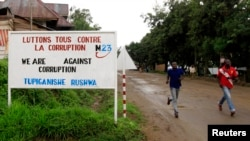 FILE - People jog past a sign, with a message by the M23 movement in their campaign against rampant corruption in the DRC, in Rutshuru, Nov. 3, 2012.