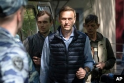 FILE - Russian opposition leader Alexei Navalny, center, arrives at court after his arrest during a protest in Moscow, May 11, 2018.