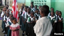 FILE - Liberian students are seen assembled to salute the flag at a Catholic school in the Liberian capital Monrovia.