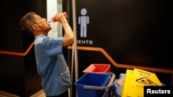 Petugas pembersih berusia 80 tahun, Lim Chin Seng, beristirahat dari pekerjaannya di sebuah pusat perbelanjaan Singapura. (Reuters/Edgar Su)