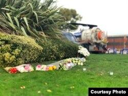 Hoa do người địa phương để lại phía đường đối diện chỗ chiếc xe đỗ sau khi phát hiện 39 người chết. (Hình: Nguyễn Hùng)