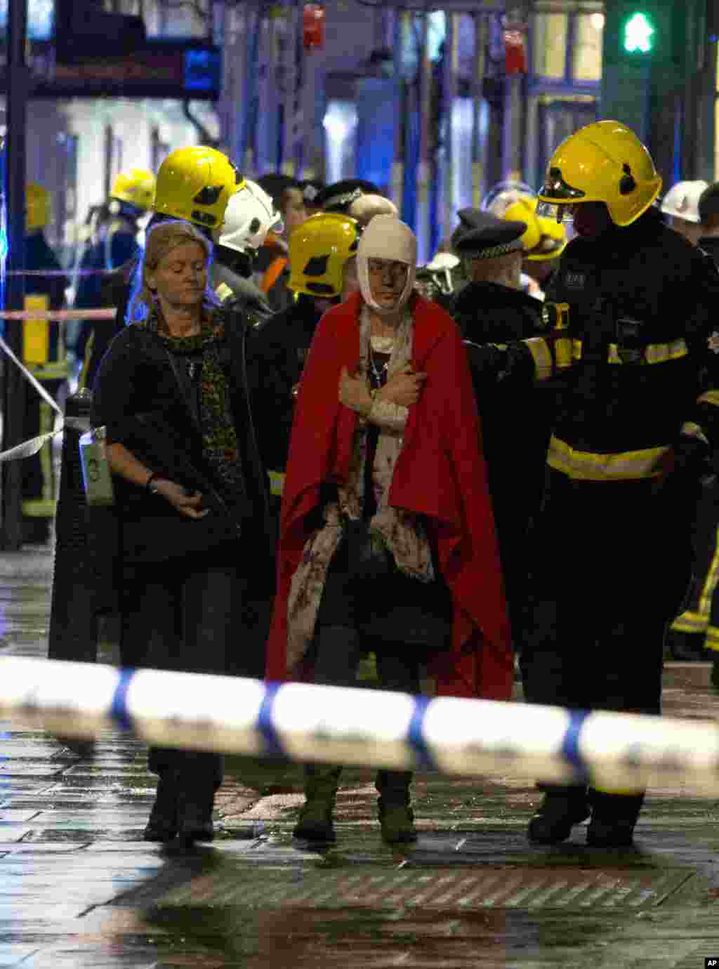 A woman walks, bandaged and wearing a blanket given by emergency services, following the partial collapse of the ceiling at the Apollo Theatre during a performance at the height of the Christmas season, Shaftesbury Avenue, central London, Dec. 19, 2013.