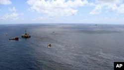 Handout picture released on November 21, 2011 by the Brazilian National Agency of Petroleum showing supply boats cleaning an oil spill around a Chevron platform operating in the Frade oil field in the Atlantic Ocean 120 km offshore Campos, northern state