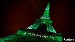 "FILE - The Eiffel tower is illuminated in green with the words ""Paris Agreement is Done,"" to celebrate the Paris U.N. Climate Change agreement in Paris, France, Nov. 4, 2016."