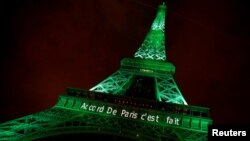 "FILE - The Eiffel tower is illuminated in green with the words ""Paris Agreement is Done,"" to celebrate the Paris U.N. Climate Change agreement in Paris, France, Nov. 4, 2016. While U.S. President Donald Trump has since expressed opposition to the agreement, Syria has joined the pact."