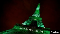 "FILE - The Eiffel Tower is illuminated in green with the words ""Paris Agreement is Done,"" to celebrate the day on which the Paris Agreement to fight climate change entered into force, Nov. 4, 2016."