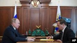 Le président russe Vladimir Poutine, à gauche, s'entretient avec le Premier ministre russe Dmitri Medvedev lors de leur réunion à Moscou, en Russie, 10 avril 2018.
