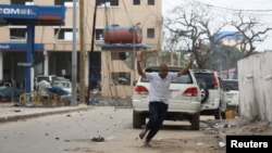 A man raises his hands as he runs from the scene of a suicide bomb attack outside the Hotel Naso-Hablod in Somalia's capital, Mogadishu, June 25, 2016.