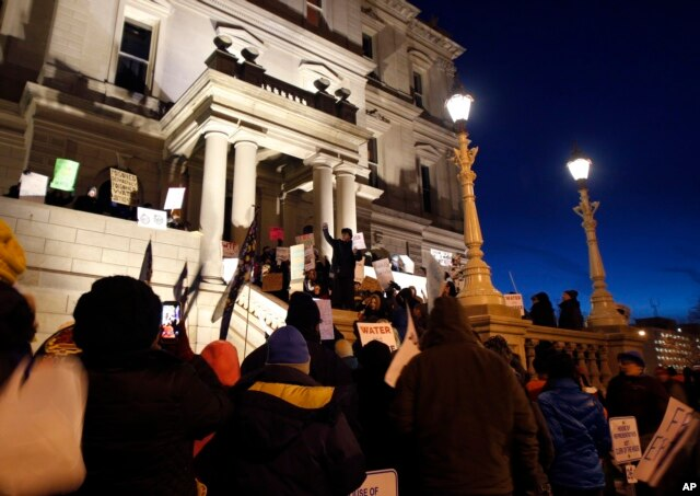 With a toxic water crisis gripping the city of Flint, protesters gather outside the Capitol in Lansing, Mich., before Gov. Rick Snyder's State of the State address, Jan. 19, 2016.