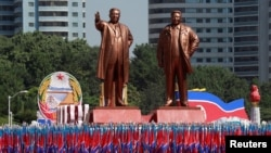 People carry flags in front of statues of North Korea founder Kim Il Sung, left, and late leader Kim Jong Il during a military parade marking the 70th anniversary of North Korea's foundation in Pyongyang, North Korea, Sept. 9, 2018.