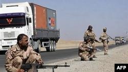 Các nhân viên an ninh tư nhân canh gác trên một con đường ở tỉnh Ghazni, phía tây nam thủ đô Kabul, trong lúc xe chở tiếp liệu của NATO chạy ngang