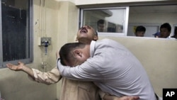Pakistanis mourn over the death of their relative killed in a firing incident, at a local hospital in Quetta, Pakistan, October 4, 2011.