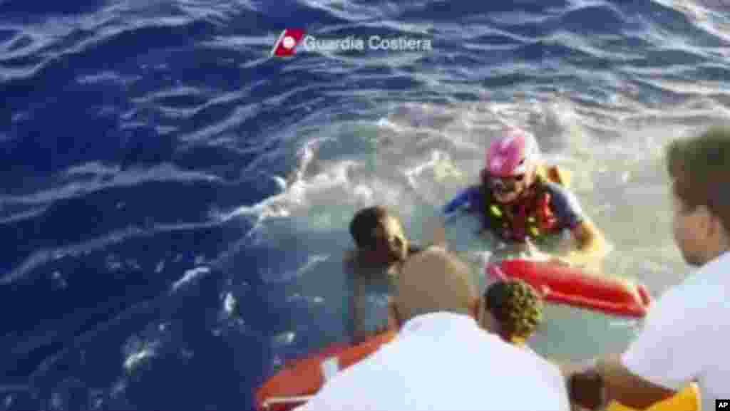 This image made from video provided by the Italian Coast Guard shows the rescue of a survivor from the ship that caught fire and sank off the island of Lampedusa, Italy, Oct. 3, 2013.