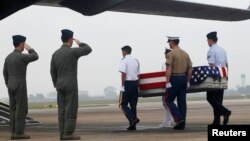 FILE - Pilots salute as U.S. soldiers carry a casket containing human remains, believed to belong to a U.S. servicemen missing in action during the Vietnam War, during a repatriation ceremony at Noi Bai airport in Hanoi, November 2012.