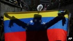 وینزویلا میں ایک حکومت مخالف کارکن آزادی کے ہیرو سائمن بولیور کے کاسٹیوم میں قومی پرچم کے ساتھ مظاہرہ کر رہا ہے۔ 24 جولائی 2017