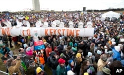 "Protestors gather at the National Mall in Washington calling on President Barack Obama to reject the Keystone XL oil pipeline from Canada, as well as act to limit carbon pollution from power plants and ""move beyond"" coal and natural gas, Feb. 17, 2013."