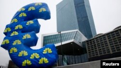 FILE - An inflated euro sign is seen outside the new headquarters of the European Central Bank (ECB) in Frankfurt, Jan. 22, 2015.