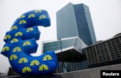 An inflated euro sign is seen outside the new head quarters of the European Central Bank (ECB) in Frankfurt, Jan. 22, 2015.