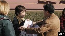 Cảnh sát mặc thường phục ngăn Jonathan Lee (giữa) mở tấm biểu ngữ của em gần Quảng trường Thiên An Môn, ngày 22/11/2010