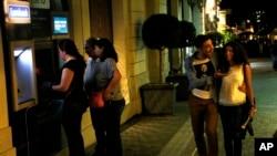 星期一早晨,一对希腊夫妇路过雅典的自动取款机。