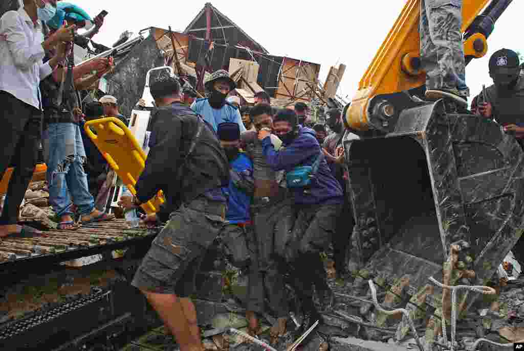 Rescuers assist a survivor pulled out from the ruin of a government building collapsed during an earthquake in Mamuju, West Sulawesi, Indonesia.
