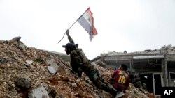 Seorang tentara Suriah menempatkan bendera nasional Suriah saat bertempur dengan pejuang pemberontak timur dari Aleppo, 5 Desember 2016. (AP Photo/Hassan Ammar).