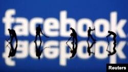 Các tượng người trước biểu tượng Facebook.