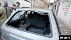 8일 예멘 사나에 폭탄 테러가 발생한 가운데, 사람들이 파손된 차량 주변에 몰려있다.
