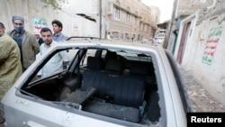 Warga berkumpul di dekat sebuah mobil yang rusak akibat ledakan bom di luar rumah pria Houthi Syiah di Sanaa (8/12). (Reuters/Khaled Abdullah)