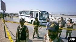 Binh sĩ bán quân sự Pakistan canh gác bên cạnh chiếc xe buýt bị hư hại sau vụ nổ bom ở Karachi, ngày 26/4/2011