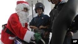 Petugas sebuah pom bensin di Jakarta berpakaian ala Sinterklas sebagai bagian perayaan Natal. (Foto: Dok)