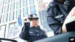 Police officers filming and checking VOA reporter's documents as he tried to get close to the site of the banned Easter service in Beijing, April 24, 2011