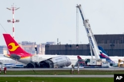 A crane works at the site of the damaged Sukhoi SSJ100 aircraft of Aeroflot Airlines in Sheremetyevo airport, outside Moscow, Russia, May 6, 2019.