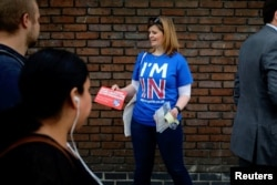 FILE - A woman campaigns in London for Britain to stay in the European Union, May 20, 2016.