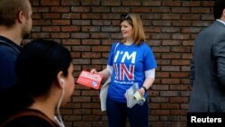 FILE - A woman campaigns in London, May 20, 2016, for Britain to stay in the European Union.