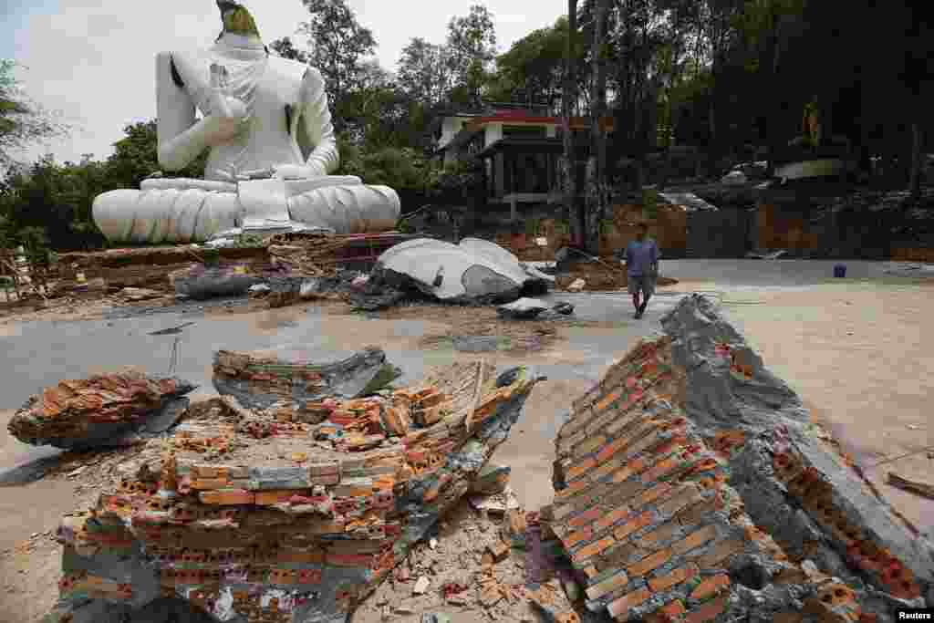 A local resident walks in front of a statue of Buddha that was damaged in an earthquake at the Udomwaree temple in Chiang Rai, in northern Thailand, May 6, 2014.