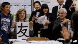 """Caroline Kennedy escribe en japonés """"tomo"""" que significa """"amigo"""" en una escuela hasta donde llegó acompañada de su esposo Edwin Schlossberg."""