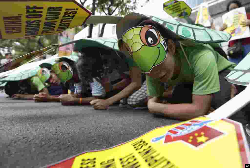 Protesters, wearing green sea turtle costumes, picket the Chinese consulate at the financial district of Makati city, Philippines, May 16, 2014.