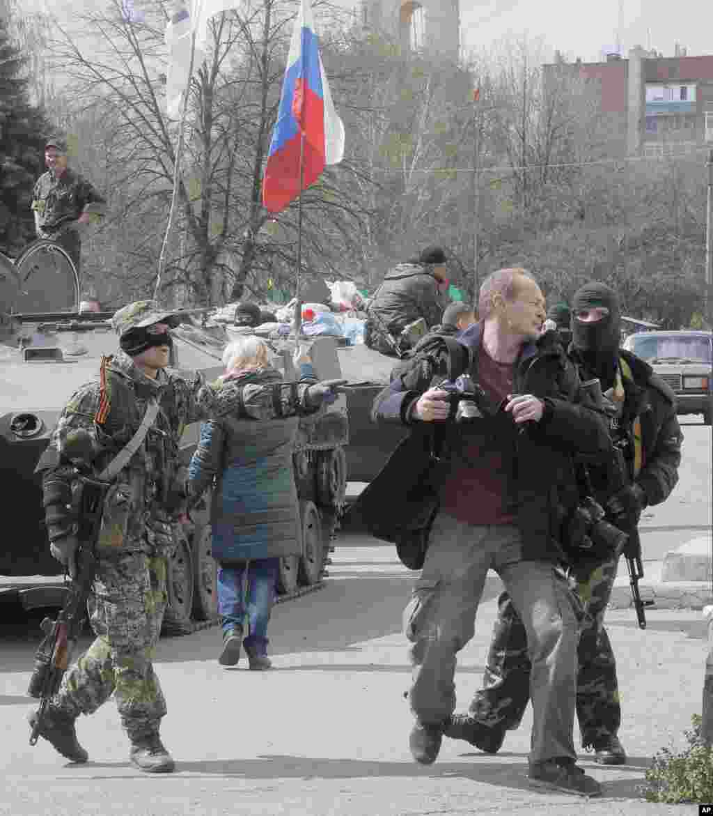 Masked pro-Russian gunmen attack a photojournalist near combat vehicles flying a Russian flag, in Slovyansk, Ukraine, April 16, 2014.