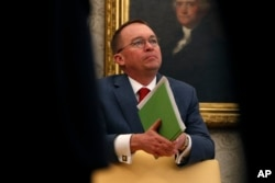 FILE - Acting White House chief of staff Mick Mulvaney listens in the Oval Office of the White House in Washington, Jan. 31, 2019.