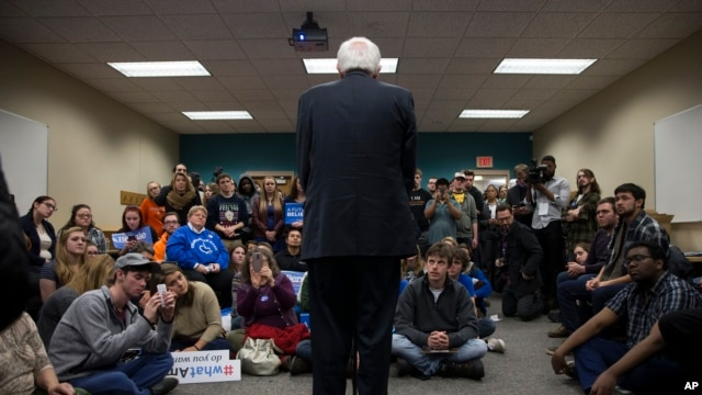 People look on as Democratic presidential candidate Sen. Bernie Sanders of Vermont speaks during a meeting with volunteers at a canvass lunch at Wartburg College in Waverly, Iowa, Jan. 30, 2016.