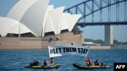 """FILE - Members of the environmental group Greenpeace hold up a sign that reads """"#LET THEM STAY"""" in front of the Opera House in Sydney, Australia, Feb. 14, 2016."""