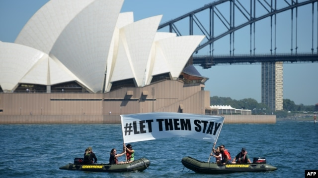 """Members of the environmental group Greenpeace hold up a sign that reads """"#LET THEM STAY"""" in front of the Opera House in Sydney, Australia, Feb. 14, 2016. A hospital in Brisbane has refused to send an asylum-seeker baby back to detention in Nauru as momentum builds across the country against offshore Pacific camps for used by the government for processing refugees who try to get to Australia."""