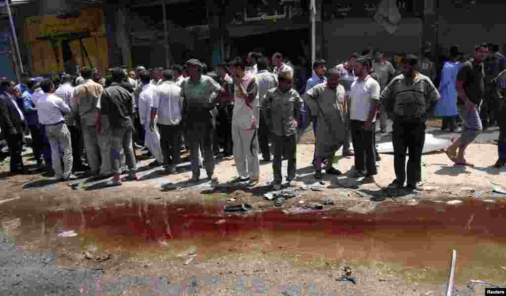 Residents look at a pool of blood after a car bomb attack in Karbala, south of Baghdad, April 29, 2013.