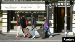Asian tourists walk past a luxury watch shop in the Swiss alpine resort Interlaken, Switzerland, Nov. 17, 2015. Europe's travel industry could lose over $1 billion in revenues because of the impact of the Paris attacks, analysts say.