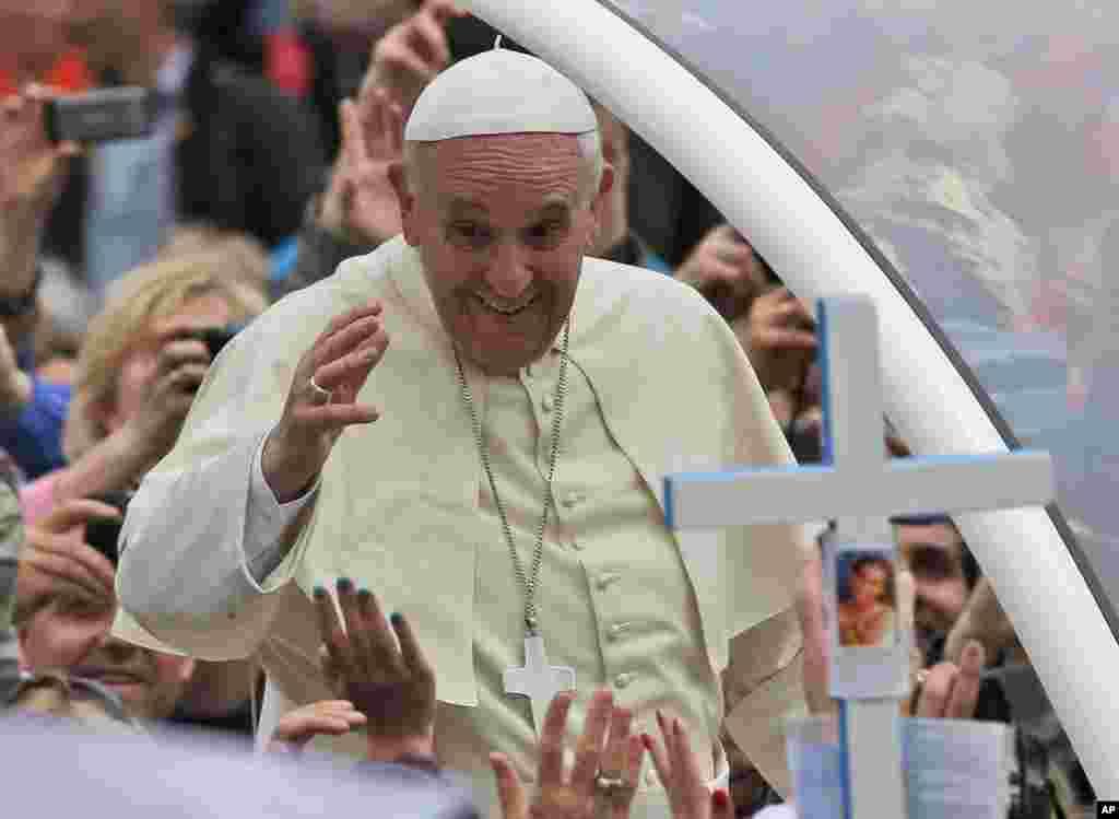 Paus Fransiskus melambaikan tangan pada umat ketika melewati kerumunan setelah memimpin upacara kanoninasi di Lapangan Santo Petrus, Vatikan, 27 April 2014.